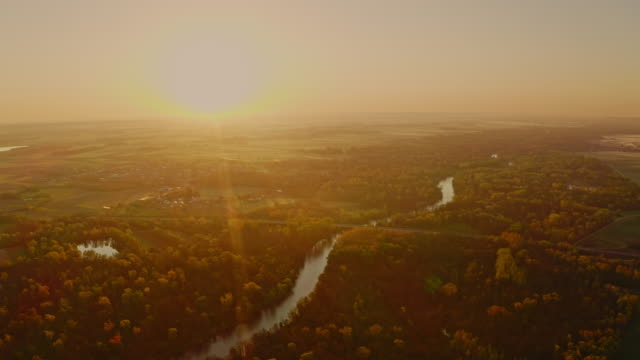aerial drone rising above the river at sunrise - речной канал стоковые видео и кадры b-roll