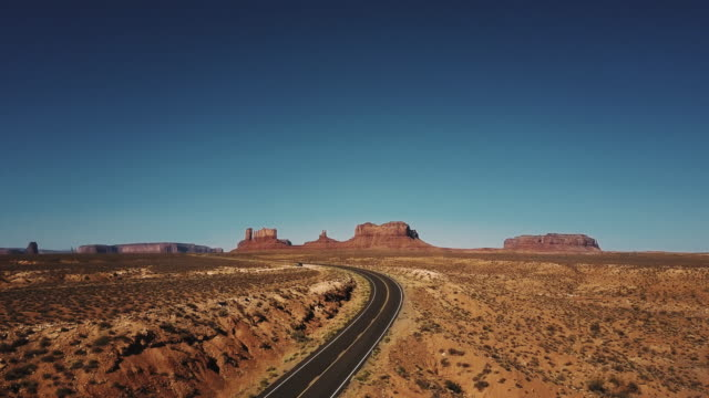 Drone rising up above empty desert road to reveal amazing endless wide open spaces of sunny Monuments Valley in USA.