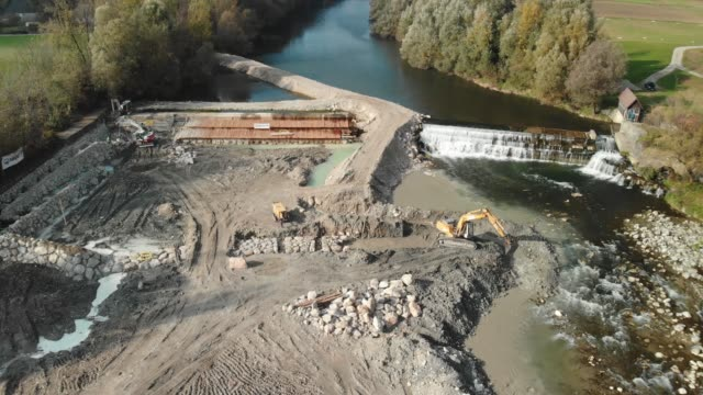 Drone shoot of excavator digging up a pit for new dam on the river Aerial view of dam being reconstructed, shoot with a drone. Constructing a new dam with the help of construction machinery. Digging the pit with excavator. crane construction machinery stock videos & royalty-free footage
