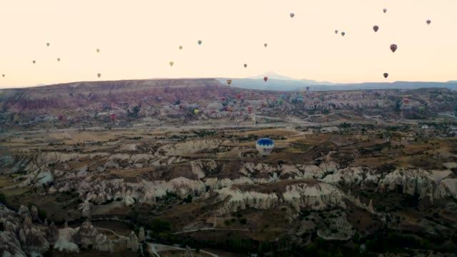 vídeos de stock, filmes e b-roll de drone disparado: balões de ar quente 4k cidade da caverna em cappadocia, turquia - país área geográfica