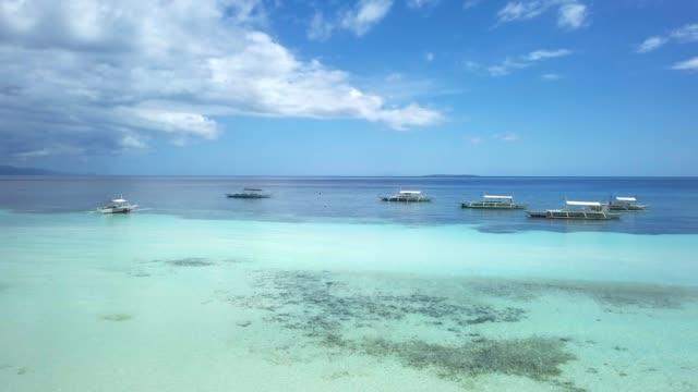 4k 無人駕駛飛機在綠松石純淨水中拍攝熱帶島嶼和小船的鳥瞰圖 - 東南 個影片檔及 b 捲影像