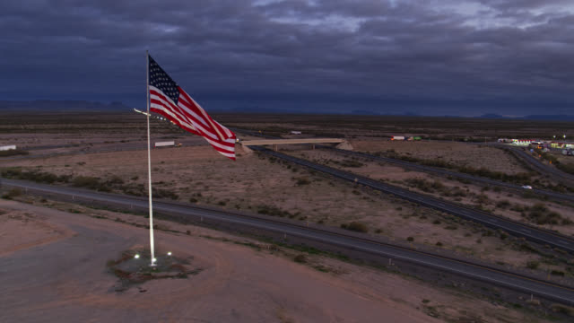 drone shot zbliża się masywna flaga usa flying over truck stop - american flag filmów i materiałów b-roll