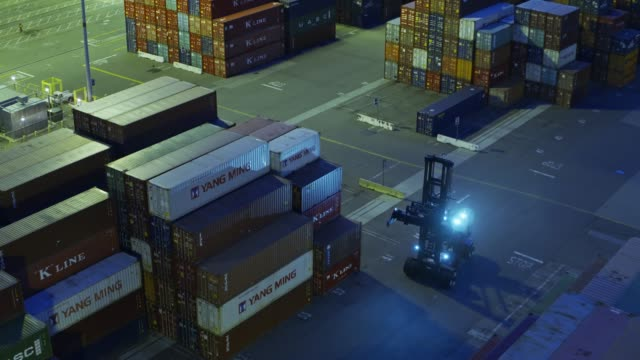 Drone Shot Circling Around Top Handler in Shipping Container Yard - vídeo