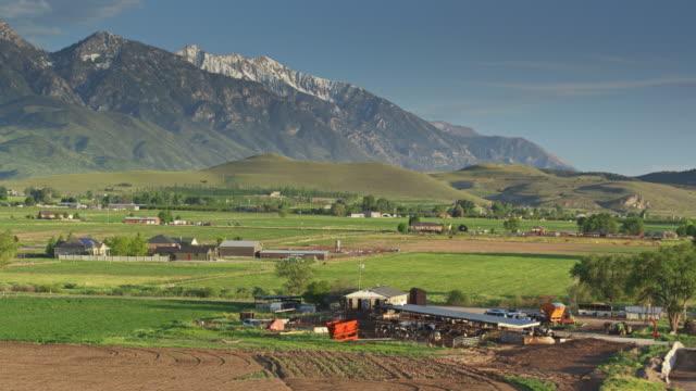 vídeos de stock e filmes b-roll de drone shot circling around utah dairy farm - rancho quinta