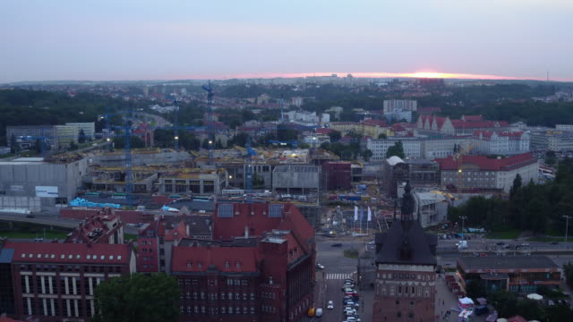 Drone shot during the sunset in Gdansk - Targ Sienny. Footage captures cranes working on Targ Sienny during the sunset and the wide panorama of south-west part of the city. gdansk stock videos & royalty-free footage