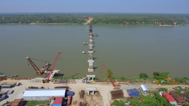 drone shot : fly back revealing the construction bridge starting from the riverbank aerial drone shot : fly back revealing the construction bridge starting from the riverbank back to back stock videos & royalty-free footage