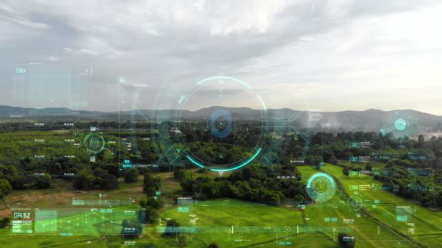 vídeos de stock, filmes e b-roll de drone tiro voando vista aérea com interface de usuário gráfico de texto barra e alvo elemento de ponteiro futurista e tecnologia cibernética - multicóptero
