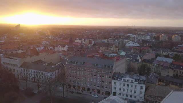 Drohne geschossen unten über Stadt Lund und hinunter nach Lund Universität Gebäude fliegen. Luftaufnahme der Stadt Skyline bei Sonnenuntergang – Video