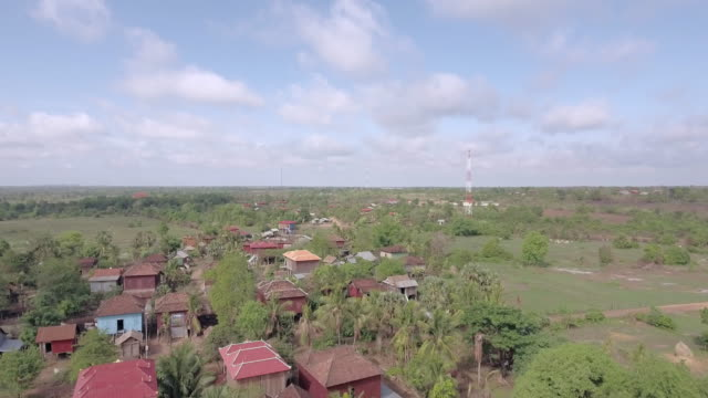 drone shot : flying over a typical south-east asian village among tropical vegetation - cambogia video stock e b–roll