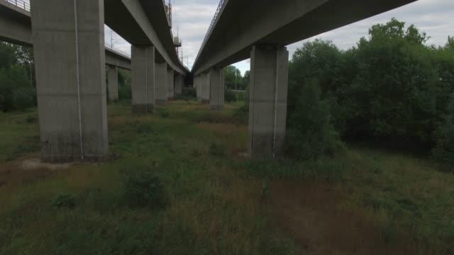Drone shot flying under high bridge
