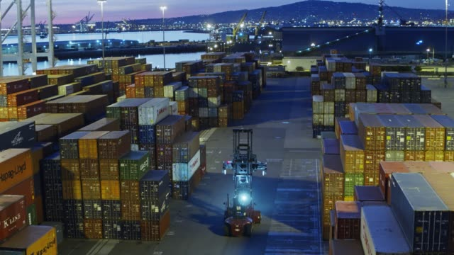 Drone Shot Following Top Handler Through Shipping Container Terminal - vídeo
