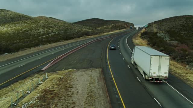 vídeos de stock e filmes b-roll de drone shot following truck up hill on interstate in west texas - cartografia