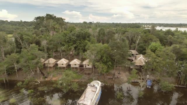 vídeos y material grabado en eventos de stock de drone disparó a girl saludando en bungalows en la selva amazónica - viaje a sudamérica