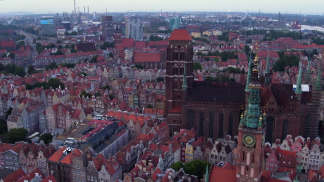 Drone shot in the evening - vivid Gdansk old architecture in a wide perspective. Flamish style, monumental historic st. Mary's Basilica, Artus Court, Gdansk shipyard in the background. gdansk stock videos & royalty-free footage