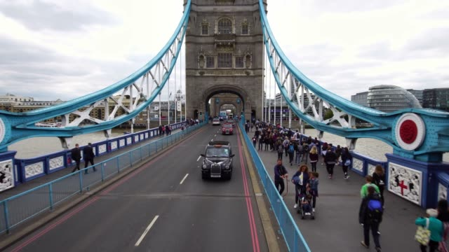 Drone shot of a black taxi cab driving on the iconic Tower Bridge in London, Great Britain