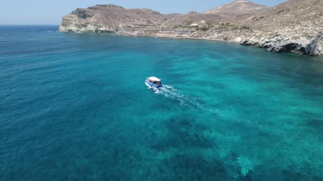 4k drone shot of a boat near santorini - morze egejskie filmów i materiałów b-roll