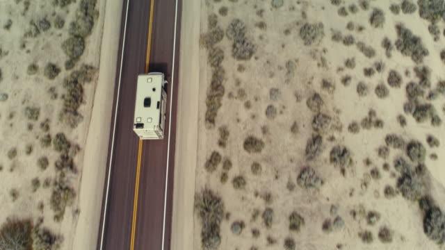 stockvideo's en b-roll-footage met drone die van een kampeerauto op een weg door de woestijn mojave wordt ontsproten - caravan
