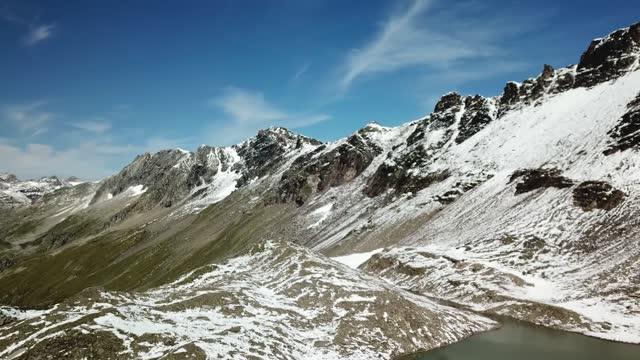 vídeos de stock, filmes e b-roll de um drone disparou de um lago nas proximidades de feldseekopf, na áustria. o lago é cercado por neve, cobrindo parcialmente as encostas pedregosas dos alpes. o lago é cercado por picos afiados e íngremes. calma - tyrol state austria