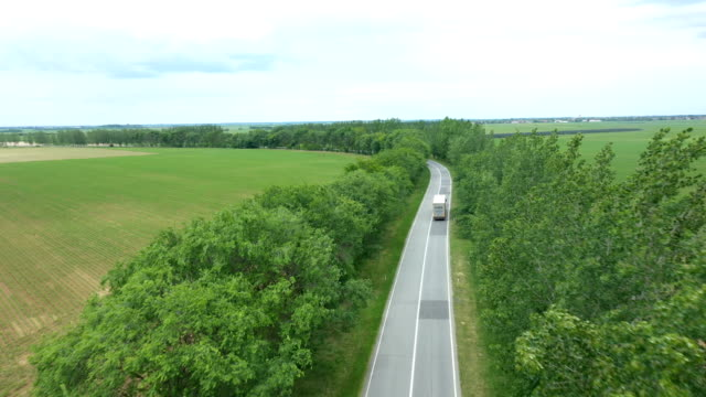 Drone shot of a lonely road in a vast field, a lorry is driving through the frame.