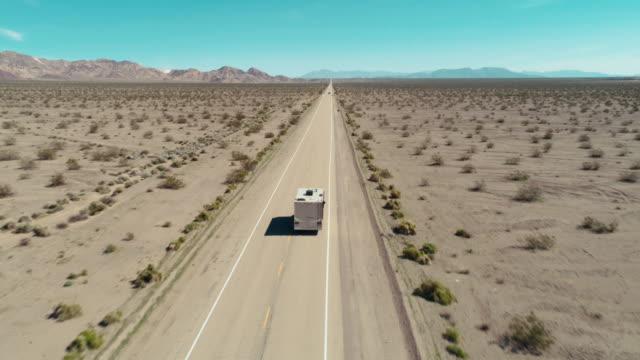 stockvideo's en b-roll-footage met drone die van een rv wordt ontsproten die op een lange weg door de woestijn mojave drijft - caravan