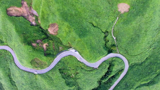 drone shot of aso mountain field and winding road - strada tortuosa video stock e b–roll