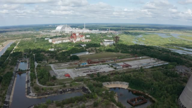 Drone shot of Chernobyl nuclear power plant Aerial shot of power plant buildings, safe confinement and unfinished reinforced concrete cooling towers in Chernobyl exclusion zone. Drone view of former power plant closed after meltdown time zone stock videos & royalty-free footage