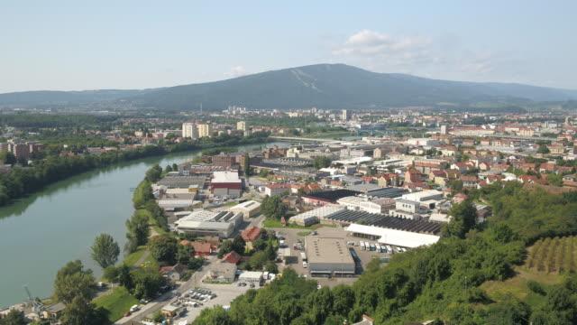 nehrin yanındaki şehrin drone çekimi - styria stok videoları ve detay görüntü çekimi