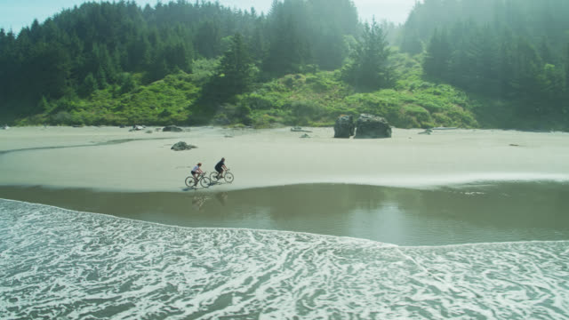 Drone Shot of Cyclists Riding Around on the Beach in Oregon