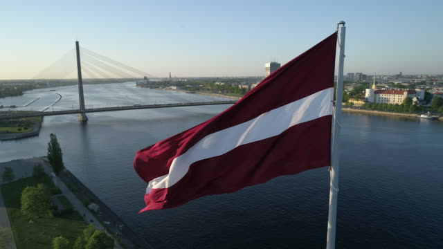 drone shot of flag of latvia in riga - латвия стоковые видео и кадры b-roll