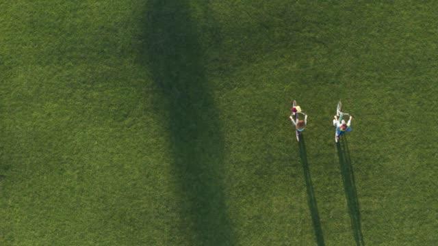 Drone shot of lgbt couple biking through park lawn