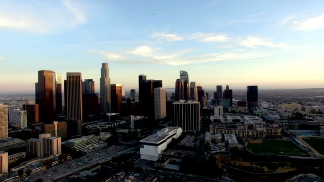 Drone shot of Los Angeles skyline below plane and helicopter video