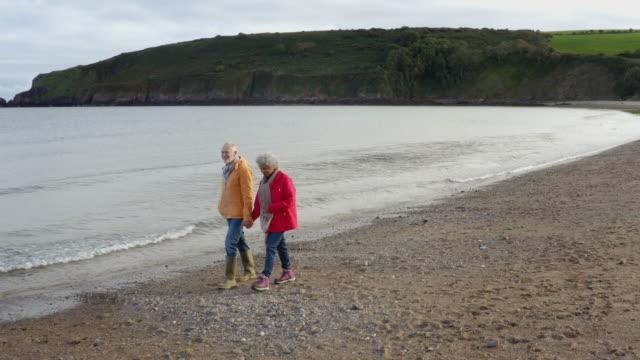 冬のビーチ休暇で海岸線に沿って歩く手をつないで愛するシニアカップルのドローンショット - スローモーションで撮影 - 老夫婦点の映像素材/bロール