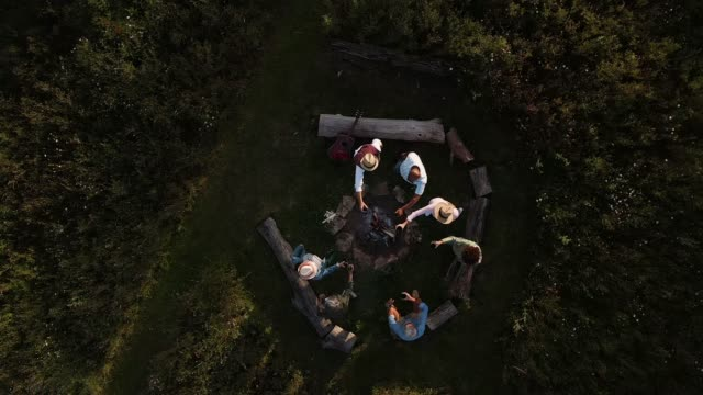 drone shot of mature friends making toast as they sit around fire at outdoor campsite - camping stock-videos und b-roll-filmmaterial