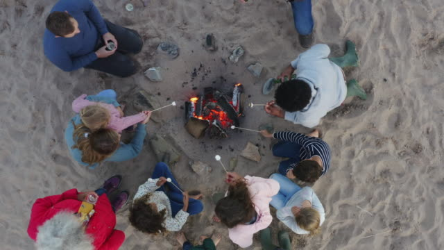 drone shot of multi-generation family toasting marshmallows around fire on winter beach vacation - falò spiaggia video stock e b–roll