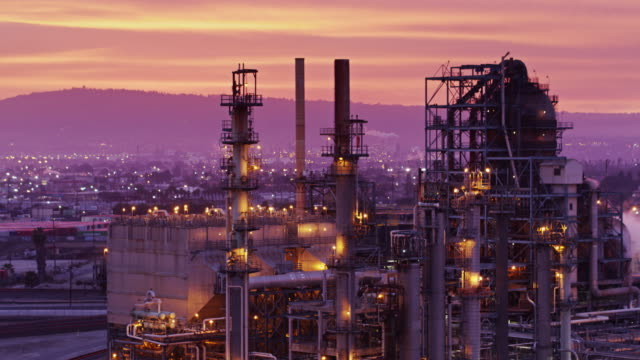 Drone Shot of oil Refinery at Sunset Backwards flight away from of a massive complex of oil refineries at the Port of Los Angeles, lit up at sunset under a dramatic pink and orange sky. oil industry stock videos & royalty-free footage