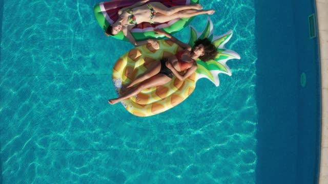 vídeos de stock, filmes e b-roll de drone disparado de mulheres relaxadas em boias na associação - piscina