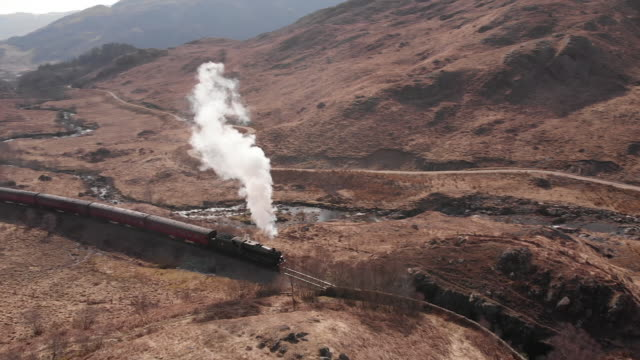 Drone shot of steam train Aerial drone shot of a steam train passing through Glenfinnan, Scotland scotland stock videos & royalty-free footage