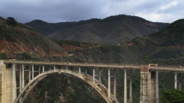 vídeos de stock e filmes b-roll de drone shot of support struts of bixby creek bridge - estrada 001