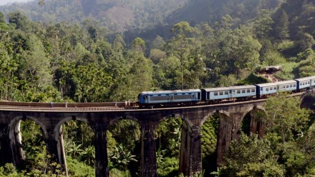 Drone shot of the famous blue train passing on old nine arch bridge in the jungle in Ella Sri Lanka