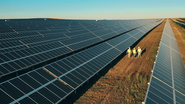 Drone shot of three solar energy specialists having a discussion at a solar power facility video