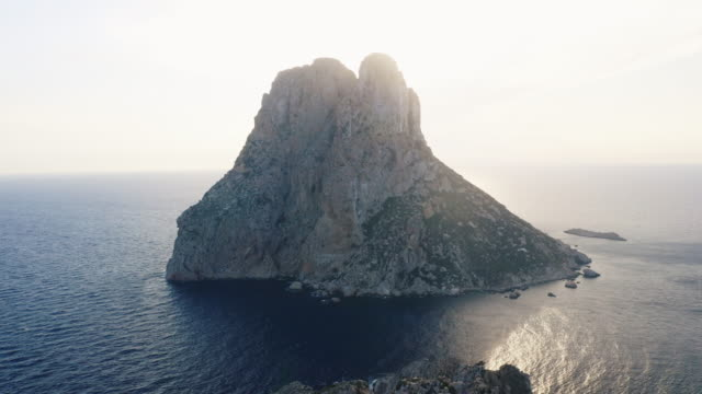 drone shot of towering cliff in ibiza surrounded by still ocean waters - ibiza filmów i materiałów b-roll