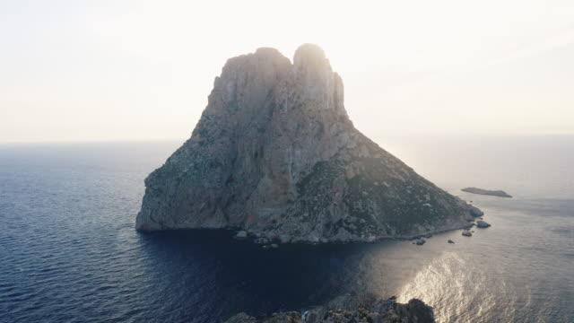 vídeos de stock e filmes b-roll de drone shot of towering cliff in ibiza surrounded by still ocean waters - ibiza