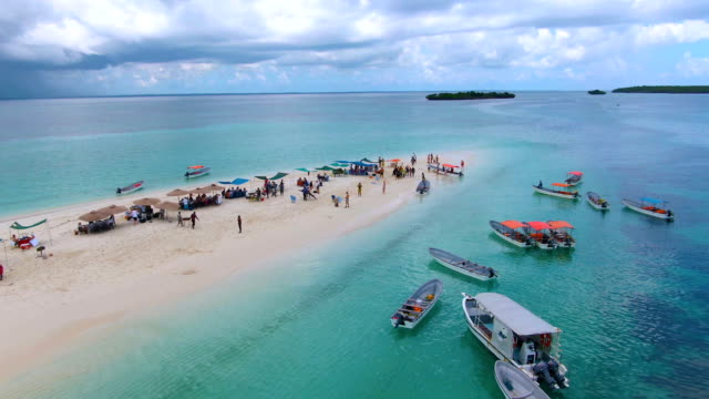 Drone shot of tropical sand island full of people and boats Drone shot of beautiful beaches, nature and ocean in Jambiani on Zanzibar island, Tanzania. tanzania stock videos & royalty-free footage