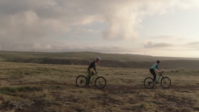 drone shot of two people (a female and a male )mountain biking on in the rocky mountains west of denver, colorado with the city below at sunrise - колорадо стоковые видео и кадры b-roll