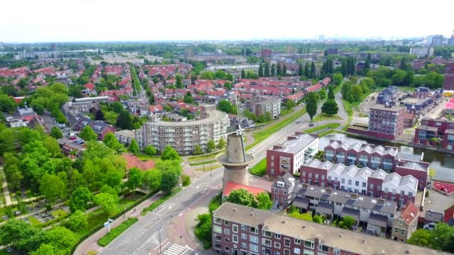 drone shot of windmill in the middle of a dutch neighbourhood - dutch architecture stock videos & royalty-free footage