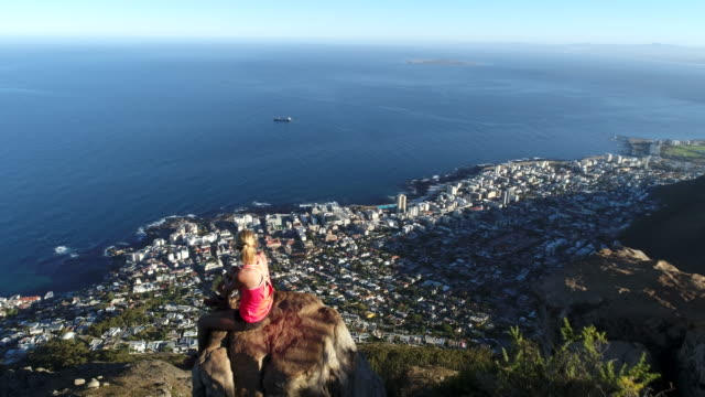 Drone shot of woman on mountain top Aerial view of a young woman on the top of Lion's head mountain in Cape Town, South Africa. cape peninsula stock videos & royalty-free footage