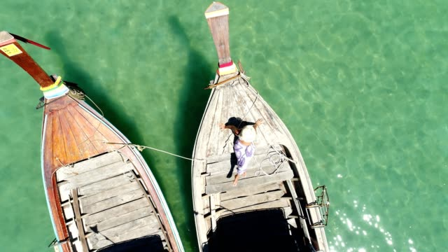 Drone shot of woman sitting on a boat enjoying nature video