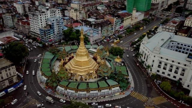 drone shot of yangon city centre flying over golden pagoda. - myanmar video stock e b–roll