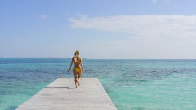 Drone shot of young woman in bikini running on wooden pier in Mexico