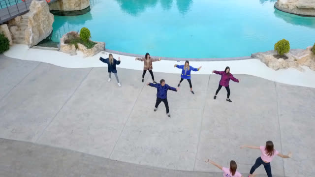 Drone shot of young women doing tai chi by the pool